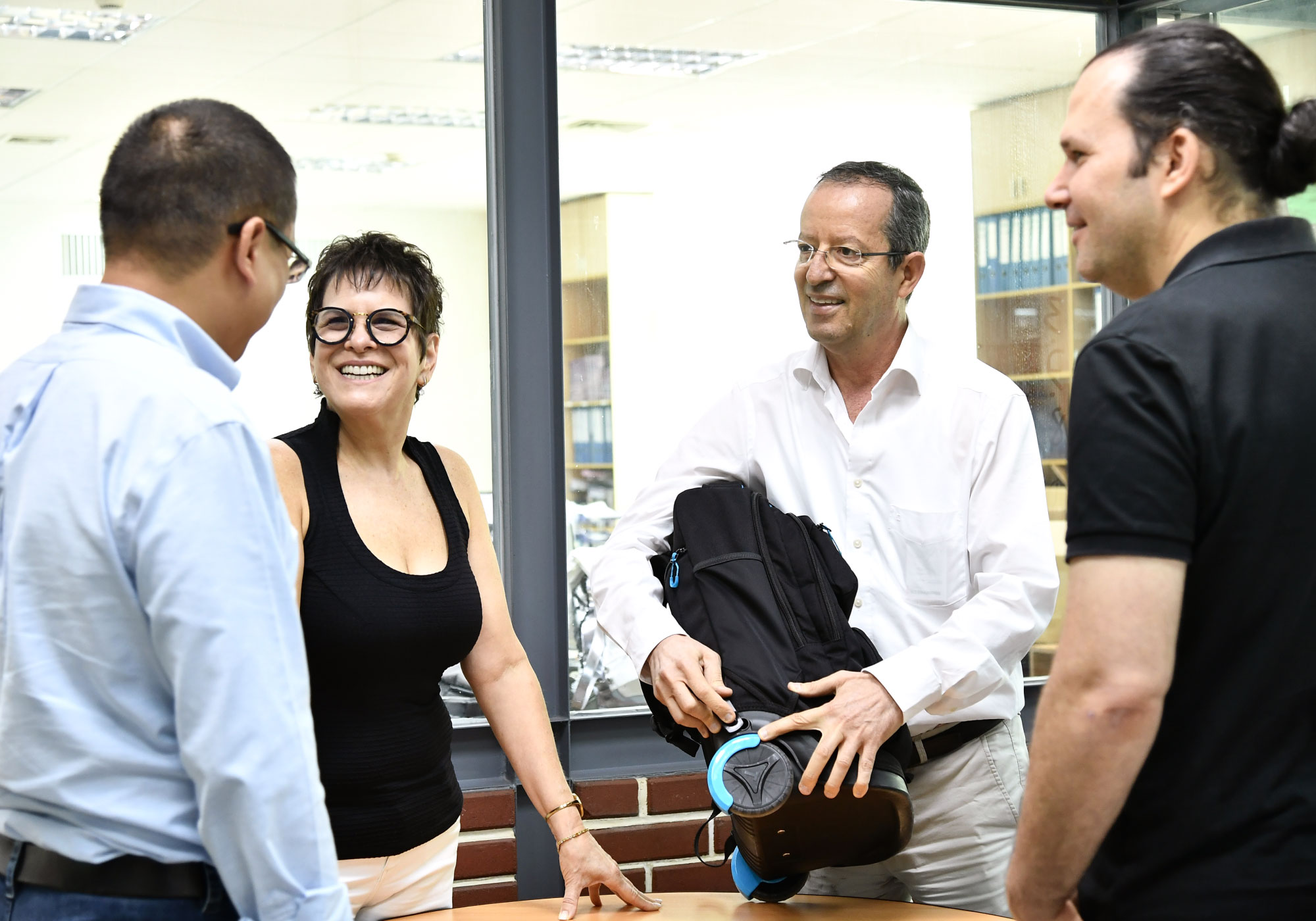 Managing director, designer, engineer and development manager discussing a technical school bag with wheels in Starry offices