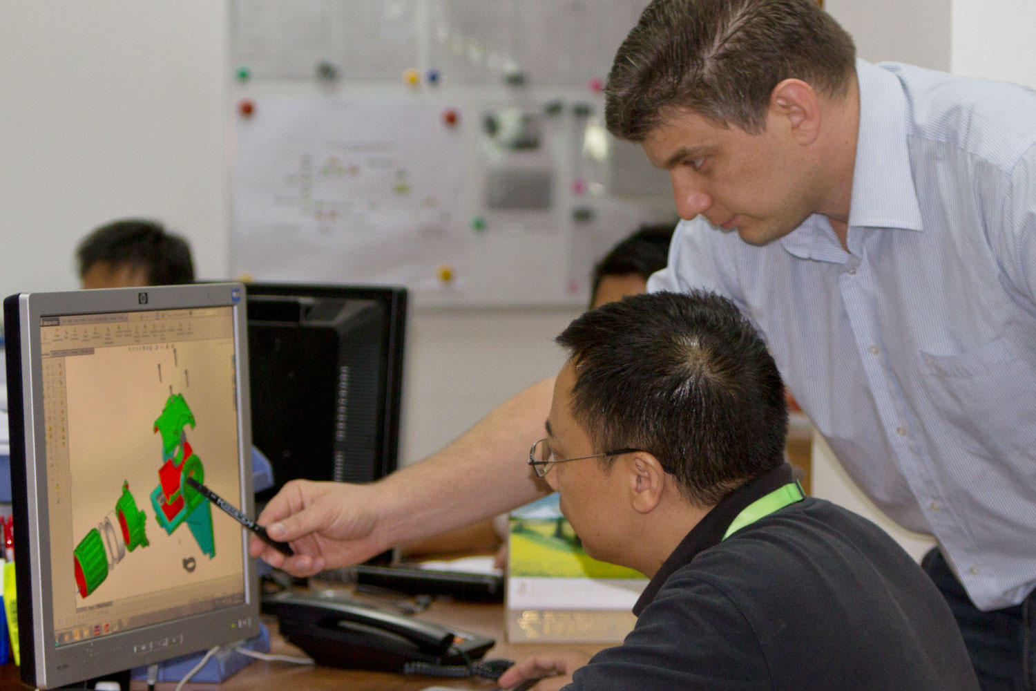 Research and development department in Tetro, China, 2 men near a computer looking at a 3D part